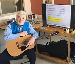 André with his guitar in front of the television screen that features song lyrics